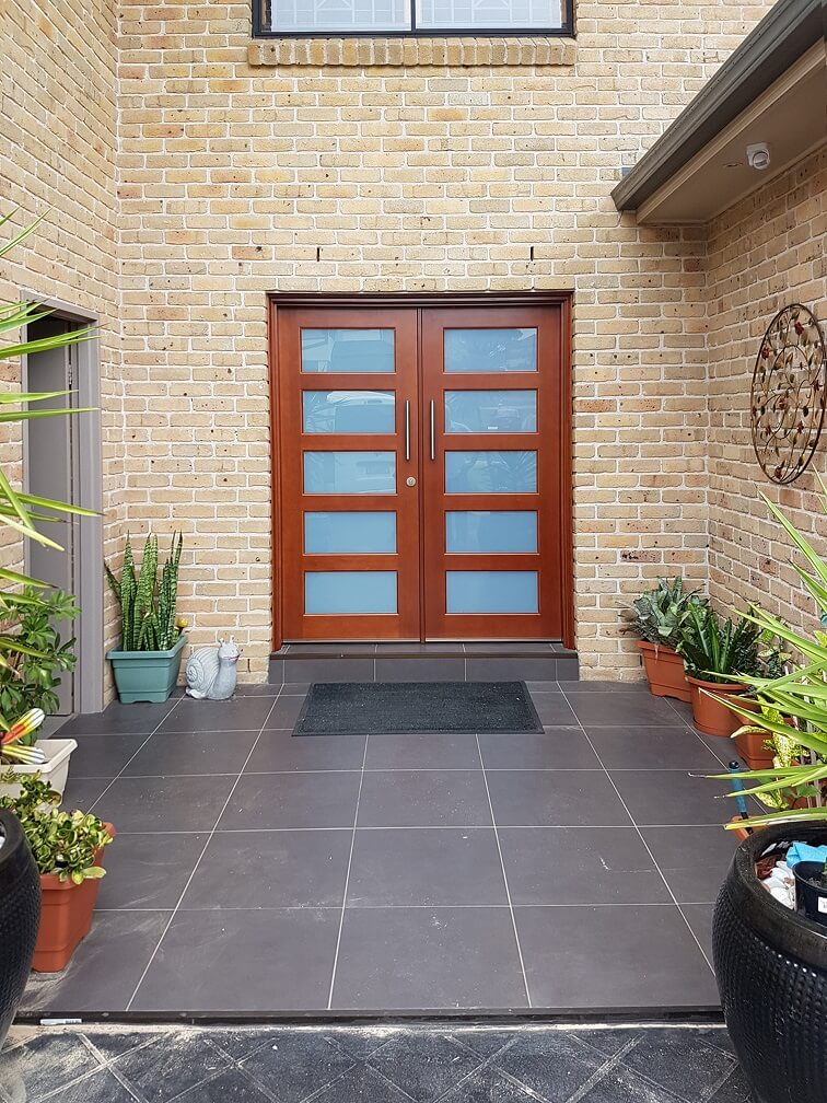 double frosted glass timber front entry doors on brick home